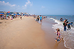Strollers and children of all ages enjoy the shallow surf at Rehoboth Beach, Delaware, USA.