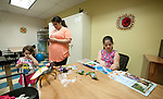 WATERBURY,  CT-051917JS03- Jacqueline Rodriguez, center, sends a text to her husband Corey Roiland, while her and her two daughters Erielle Roiland, 3, left, and Eva Roiland, 9, spend time inside River Baldwin Recreation Center in Waterbury as they wait to meet with a social worker on Friday during a social services fair. The event, organized by the Hispanic Coalition of Greater Waterbury, was held to offer help and guidance for the families displaced from their homes following the fire on Lounsbury Street. The family, like many, lost everything in the fire. <br /> Jim Shannon Republican-American