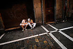 A man sits beside a street during the San Fermin Festival, on July 11, 2012, in Pamplona, northern Spain. The festival is a symbol of Spanish culture that attracts thousands of tourists to watch the bull runs despite heavy condemnation from animal rights groups. (c) Pedro ARMESTRE