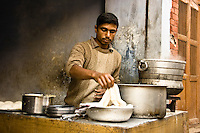 Cook rolling out dough to make chapattis - a kind of whole wheat flat bread. (Photo by Matt Considine - Images of Asia Collection)