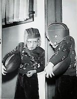 Boy with football and helmet contemplating his image in mirror. 1950's.<br />