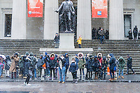 Intrepid tourists brave the cold and snow in front of the Federal Hall in New York on Tuesday, January 31, 2017. The snow will wind down by the late afternoon leaving only about an inch in the city. (© Richard B. Levine)