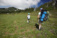 Female child and mother backpacking through meadow in Spray Park cross-country zone, Mount Rainier National Park, Washington State, USA