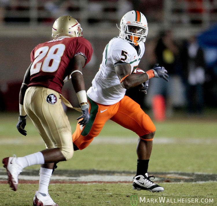 Miami running back Javarris James (5) tries to elude FSU cornerback Dionte Allen in the second half of University of Miami's 38-34 defeat of the Florida State Seminoles in Tallahassee September 7, 2009.  (Mark Wallheiser/TallahasseeStock.com)