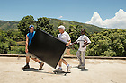 Stephen Jordan (left) carries a panel with his father. Haiti gets an average of about 8 to 10 hours of sun each day.