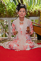 Myanmar, Burma. Bagan.  Burmese Dancer in Traditional Dress, Sitting, Holding a Small Percussion Instrument and Two Small Bells.