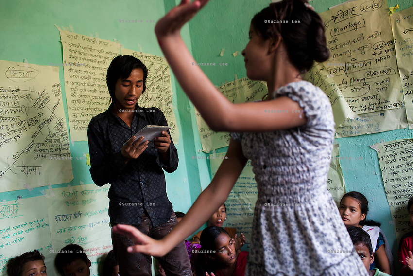 Chandraseker Shahi, 17, sings a self-written song against child marriage while Sarawati Regmi (white, age 11) dances to it at the Kishuri Sachetana Child Club in their activity center in Thahuri Tole, Chhinchu, Surkhet district, Western Nepal, on 1st July 2012. Sarawati Regmi is Pandit Dharma Raj Regmi's daughter and has ambitions to run an NGO. These Child Clubs, supported by the government, Save the Children and their local partner NGO Safer Society, advocate for child rights and against child marriages and use peer support and education to end child marriages and raise awareness. Photo by Suzanne Lee for Save The Children UK