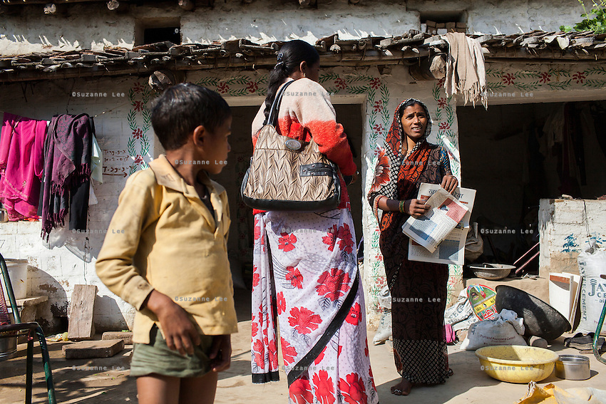 Junior community reporter Sunita (center), 22, distributes this week's Khabar Lahariya newspaper to Kamlesh Kumari (right), 28, at her house in a village in Chitrakoot, Uttar Pradesh, India on 5th December 2012. Kamlesh, a mother of 2, is a farmer, earning about 20000 rupees of sales per annum from her 2 acre farm. She dreams of becoming a journalist for Khabar Lahariya but is not able to apply since the newspaper only takes one reporter in each area, and Sunita is already working in the area. Kamlesh reads the papers out loud to her whole family and illiterate friends. Photo by Suzanne Lee for Marie Claire France.
