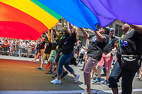 Walmart employees carry a giant rainbow flag in the annual Lesbian, Gay, Bisexual and Transgender Pride Parade on Fifth Avenue in New York on Sunday, June 29, 2014. The parade commemorates the 45th anniversary of the Stonewall Inn riots in Greenwich Village which many feel is the start of the gay rights movement in 1969. The parade is the largest gay pride parade in the world.(© Richard B. Levine)