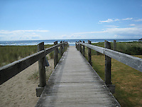 A weathered walkway stretches across the sand and dune grasses to the Pacific Ocean near Cannon Beach, Oregon USA - June 5, 2007.