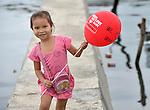 A girl walks with a balloon celebrating international solidarity with survivors in Tacloban, a city in the Philippines province of Leyte that was hit hard by Typhoon Haiyan in November 2013. The storm was known locally as Yolanda. The ACT Alliance has been active here and in affected communities throughout the region helping survivors to rebuild their homes and recover their livelihoods.