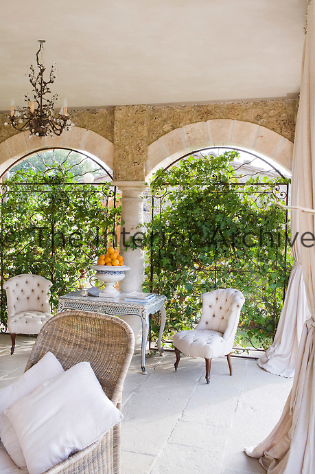 An elegant living room open to the gardens features a pair of arched windows covered with climbing plants