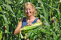 Woman harvesting Shoepeg Corn