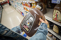 """A thirsty shopper chooses a gallon jug of Arizona's Arnold Palmer Half & Half, iced tea and lemonade, in a supermarket in New York on Monday, September 26, 2016. The popular """"King of Golf"""" passed away Sunday of complications from heart problems at the age of 87. Palmer was in the vanguard of sports marketing and was one of the highest earners in the golf world. (© Richard B. Levine)"""