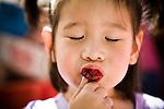 Four-year-old Alexandra Lee tastes a cherry at the Davis Farmer's Market in Davis, CA May 9, 2009.