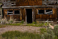 A broken window sash gives a cockeyed wink from a derelict tavern tucked away on a backroad in Nevada's Humboldt National Forest.