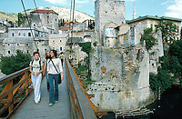 Bosnia. Mostar. A group of young modern muslim women walk on the footbridge and cross the temporary bridge. A view on the remains of the famous 15th century turkish bridge over the Neretva river. The old bridge was shelled and destroyed in 1993 by croat bombs during the bosnian war (croats against muslims). The bridge's destruction was an attack on a symbol of history, resistance and of Mostar's union between religions. A footbridge was built as an overpass to allow people to get on the other side of the city. 4.06.02 © 2002 Didier Ruef