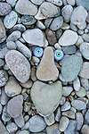 Troll face amongst beach pebbles, Claggain Bay, Islay, Scotland