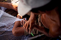 "Son, 57, makes a fishing net on the porch of his boat house on the Hau Giang River, a tributary of the Mekong River, in Chau Doc, in the An Giang Province, Vietnam. The fishing net will take five hours to complete. When the Mekong River reaches Vietnam it splits into two smaller riveres. The ""Tien Giang"", which means ""upper river"" and the ""Hau Giang"", which means ""lower river"". Photo taken on Monday, December 7, 2009. Kevin German / Luceo Images"