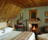 The ceiling of this snug bedroom has been lined with pine and the chimneypiece designed with shells