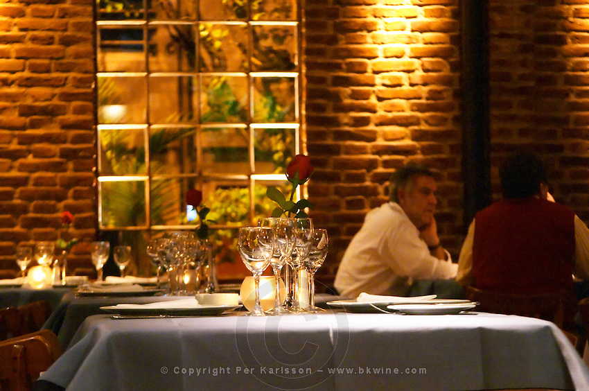 View over the restaurant dining room, tables set for dinner guest with white plate, linen napkin with black rose, silverware knives and forks, spoons wine glasses. Dinner guests. The Rosa Negra Restaurant, The Black Rose, Buenos Aires Argentina, South America