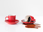 Two red espresso coffee cups, one cup with spilled coffee isolated on white background