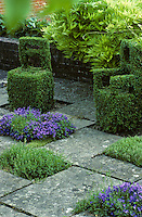A stone-flagged patio with a pair of topiary chairs