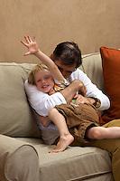 Tias Little and son, Eno, play around on the sofa
