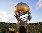 Notre Dame football players hold up their helmets in the the traditional post-game salute to the Notre Dame Stadium student section.