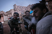 "In this Friday, Sep. 27, 2013 photo, Syrian displaced men and children gather to smoke ""narguile""  (water pipe) and chat at the sunset in the Kafr Ruma, an ancient roman ruins used as temporary shelter by those families who have fled from the heavy fighting and shelling in the Idlib province countryside of Syria. Dozens of families settled in the ancient ruins known as ""The Forgotten City"" and declared human heritage by UNESCO, when the clashes between opposition fighters and government forces broke out in the region since more than two years ago. (AP Photo)"