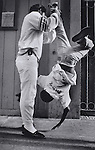 A man turns a young boy upside down in a playful gesture on the sidewalks in the tenderloin district of San Francisco, California.