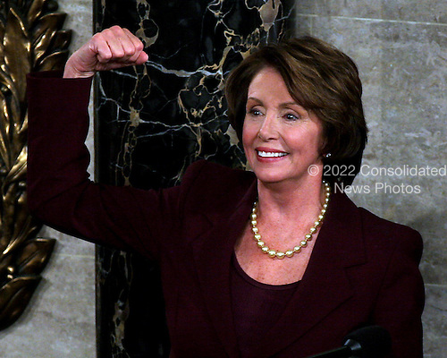 """Washington, D.C. - January 4, 2007 --  United States Representative Nancy Pelosi (Democrat of the 8th District of California) shows her """"muscle"""" after she was sworn-in as the Speaker of the United States House of Representatives in the Capitol in Washington, D.C. on Thursday, January 4, 2007.  Speaker Pelosi is the first woman in U.S. history to serve in that position..Credit: Ron Sachs / CNP"""
