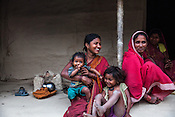 21 year old Asha Devi holds her 11 month daughter, Sita Mandal while her 3 year old son, Gaurav Mandal (centre) and mother in law, Gita Devi share a light moment in their house in Bhardaha in Saptari, Nepal.