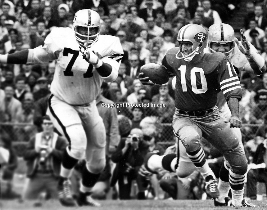 49er quarter back George Mira chased by Ike Lassiter of the Raiders. Photo by Ron Riesterer