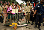 """A band of locals masquerading as illegal loggers and charcoal manufacturers made some of the more exuberant displays at Dayurejo's conservation carnival. Sign reads: """"This is a place fit as a forest prison"""""""