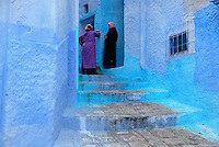Women talking in a narrow stepped street painted blue in the medina or old town of Chefchaouen in the Rif mountains of North West Morocco. Chefchaouen was founded in 1471 by Moulay Ali Ben Moussa Ben Rashid El Alami to house the muslims expelled from Andalusia. It is famous for its blue painted houses, originated by the Jewish community, and is listed by UNESCO under the Intangible Cultural Heritage of Humanity. Picture by Manuel Cohen