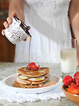 Closeup of a woman hand pouring maple syrup on pancakes with strawberries and apples