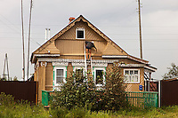 Korovikha, Ivanova Region, Russia, 05/08/2012..A resident working on a traditional brightly painted Russian wooden home in Korovikha, some 200 miles east of Moscow.