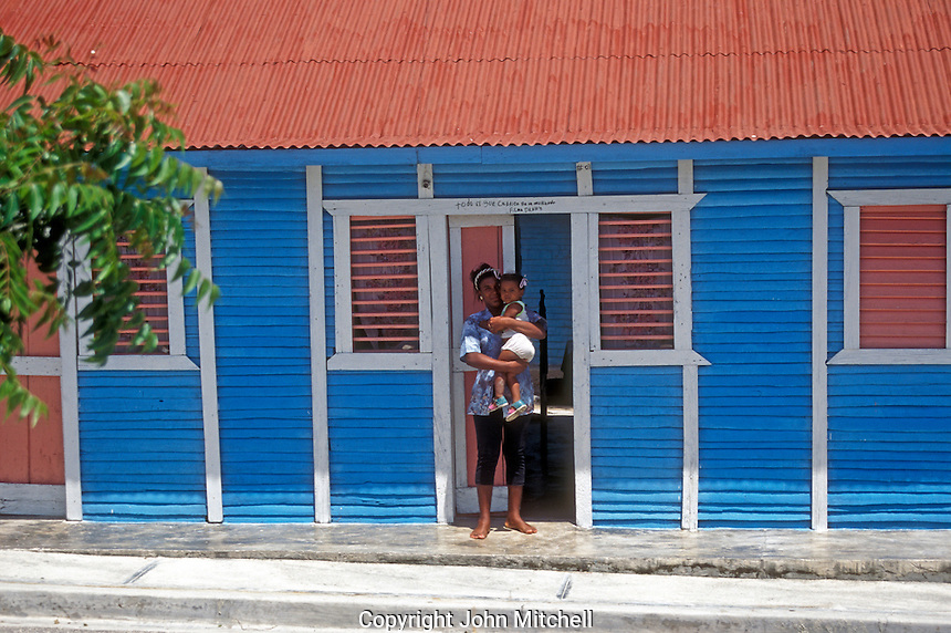 Mother and daughter outside their colourful wooden house in rural Barahona, Dominican Republic