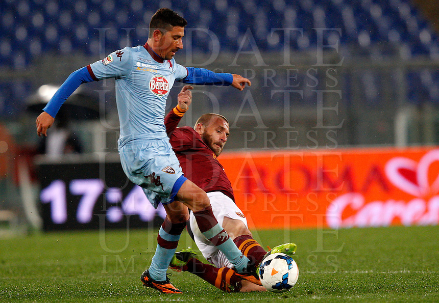 Calcio, Serie A: Roma vs Torino. Roma, stadio Olimpico, 25 marzo 2014.<br /> Torino midfielder Giuseppe Vives is tackled by AS Roma midfielder Daniele De Rossi, right, during the Italian Serie A football match between AS Roma and Torino at Rome's Olympic stadium, 25 March 2014.<br /> UPDATE IMAGES PRESS/Riccardo De Luca
