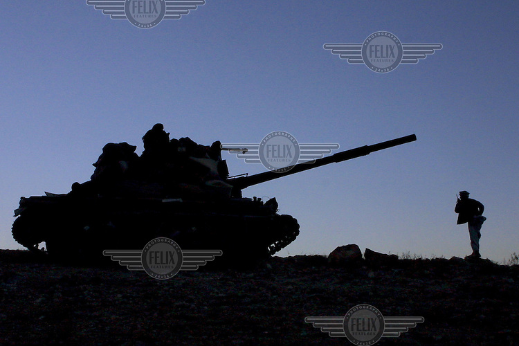 A tank is silhouetted againsty the skyline as Northern Alliance fighters take up positions while fighting Al Qaeda in the Tora Bora mountains.