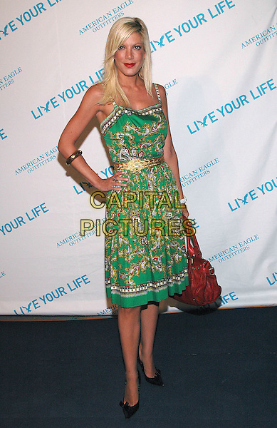 """TORI SPELLING.American Eagle Outfitters' """"Live Your Life Contest"""" winners at the Union Square flagship store in Manhattan, New York, New York..July 27th, 2005  .Photo Credit: Patti Ouderkirk/AdMedia.full length red leather bag green pattern print dress gold belt hand on hip braacelet.www.capitalpictures.com.sales@capitalpictures.com.© Capital Pictures."""