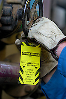 Applying of equipment isolation tag in industrial location.<br />