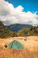Woman approaching camp site on grassy clearing next to Perth River with great mountain views, South Westland, West Coast, New Zealand