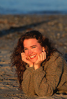 woman smiling in a sweater at the beach