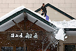 A man clears snow off his roof along the the main street at Hirafu, Japan on Feb. 8 2010. An average of 15 meters of snow falls in the Niseko area each year