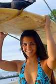 Young local girl carrying surf board on her head