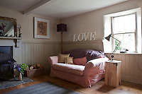 Wooden letters spelling out the word LOVE are displayed on the wall of the sitting room above a comfortable sofa