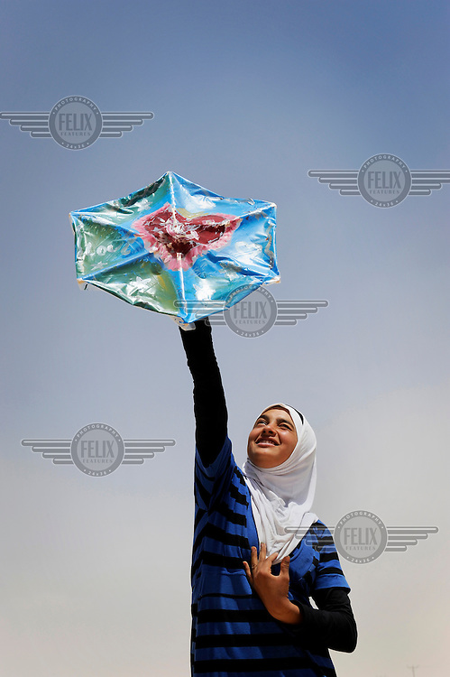Syrian refugee Reema holds up a kite which she made herself with her personal message of peace for her country. Reema fled Syria with her parents and siblings nearly nine months ago. With her love for painting she painted a big smiling heart on her kite and explained, 'Every sad heart needs to smile, even the ones that feel pain. I know my heart will smile when I return to Syria, but also the kindness among my new friends here around me makes my heart smile.' /Felix Features