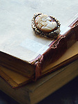An old cameo brooch in a golden frame, laid on vintage books.